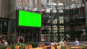 注意大屏幕的人们在有绿色屏幕的波茨坦广场compositing 股票视频