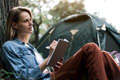 注意她的想法的被启发的妇女在旅途期间 免版税图库摄影