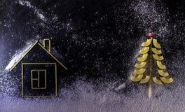 注意由雪、积雪的圣诞树和面团房子d 免版税库存图片