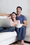 注意电影的一对笑的夫妇的纵向 库存图片