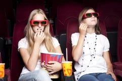 注意电影的二个美丽的女孩在戏院 免版税库存照片