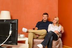 注意电视拥抱的坐的扶手椅子的新夫妇 免版税库存图片