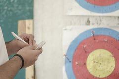 注意的手反对射箭目标 免版税库存图片