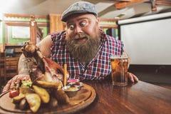 注视不健康的食物的惊奇的肥胖人 库存图片