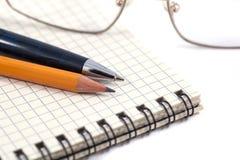 注视与笔、铅笔和黏合剂笔记本的玻璃 免版税库存照片