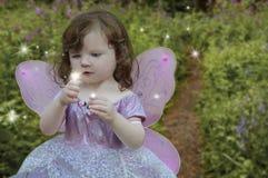注视发光的女孩神仙在她的手上 免版税库存图片