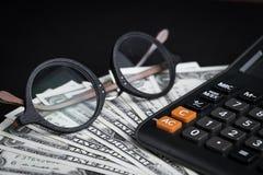 注视在堆的玻璃美元钞票和计算器有blac的 免版税库存照片