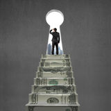 注视在有关键孔的金钱台阶顶部 免版税库存照片