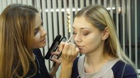 注视应用眼影膏粉末,美丽的妇女面孔的构成妇女 股票视频