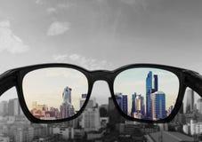 注视看对城市视图的玻璃,集中于玻璃透镜 免版税库存图片