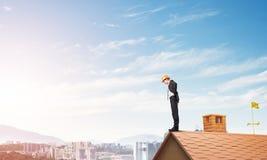 注视着下来从屋顶和现代都市风景的商人背景 混合画法 库存图片