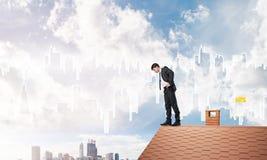 注视着下来从屋顶和现代都市风景的商人背景 混合画法 免版税库存照片