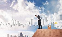 注视着下来从屋顶和现代都市风景的商人背景 混合画法 库存照片