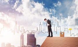 注视着下来从屋顶和现代都市风景的商人背景 混合画法 免版税图库摄影