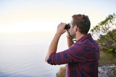注视着与他的双筒望远镜的天际的年轻人 免版税库存图片