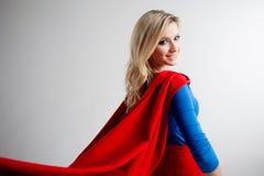 注视着入距离的超级英雄妇女权利 superheroine的图象的年轻和美丽的金发碧眼的女人,后面 免版税图库摄影