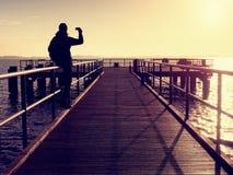 注视着在从木旅馆码头的海的敞篷的一个人早晨 免版税库存照片