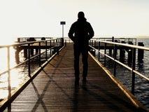 注视着在从木旅馆码头的海的敞篷的一个人早晨 免版税图库摄影