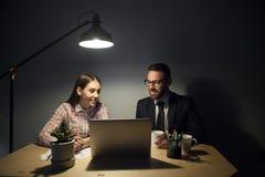 注视着在膝上型计算机的微笑的愉快的商务伙伴夜班 库存照片