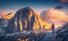 注视着在高山峰顶的足迹的年轻女人日落 库存照片