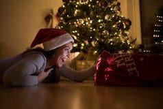 注视着惊奇她的圣诞礼物的美丽的年轻女人 库存照片