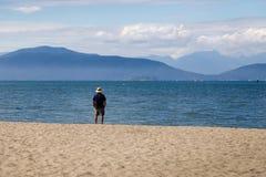 注视着海洋和山的美丽的景色的一个退休的人在一好日子 免版税库存照片
