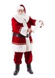 注视着淘气和尼斯名单的圣诞老人 库存照片