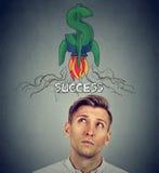 注视着火箭在头上的美元的符号的体贴的年轻人 图库摄影