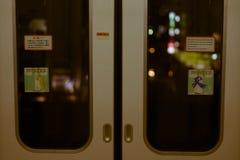 注视着火车门,当驾驶通过东京夜时 免版税库存照片