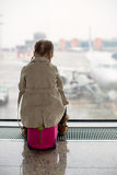 注视着窗口的小女孩机场终端 库存照片