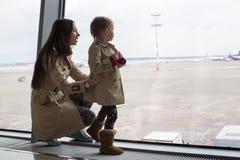 注视着窗口的母亲和小女儿机场终端 免版税库存照片
