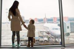 注视着窗口的母亲和小女儿机场终端 免版税库存图片