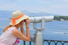 注视着通过公开双筒望远镜的女孩海边佩带的桃红色 库存图片