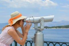 注视着通过公开双筒望远镜的女孩海边佩带的桃红色 库存照片