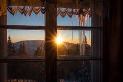 注视着通过窗口山冬天日落 免版税库存图片