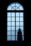 注视着通过窗口的妇女可爱的降雪 免版税库存图片
