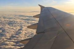 注视着通过窗口航空器在飞行期间的日落 库存图片