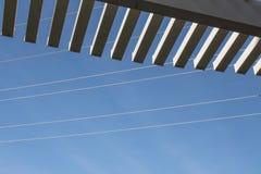 注视着通过荫径的板条的倾斜看法蓝天和输电线 免版税库存照片