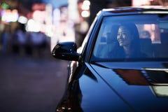 注视着通过车窗的微笑的妇女城市夜生活 库存图片