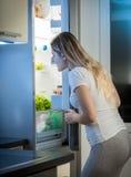注视着里面开放冰箱的年轻饥饿的妇女夜 图库摄影