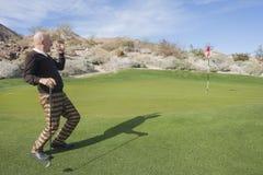 注视着高尔夫球场的全长资深男性高尔夫球运动员 免版税库存图片