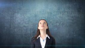 注视着copyspace的美丽的女实业家 站立在藏青色背景 库存图片