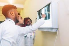 注视着X-射线医疗保健,医疗和放射学概念的年轻医生多种族队  库存照片