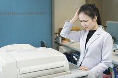 注重看纸的年轻亚裔女实业家困住在印刷品 库存图片