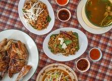 泰国东北传统食物,烤鸡,混乱油煎的面条,番木瓜沙拉,酸辣鸭子 库存照片