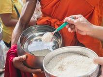 泰国人投入食物给修士`施舍在最后佛教被借的天的滚保龄球的s 免版税图库摄影