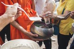泰国人投入食物给修士`施舍在最后佛教被借的天的滚保龄球的s 免版税库存图片