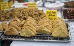 泰国传统食物油煎了在钢滤栅的豆腐在与这个食物和价格的名字一个黄牌的泰国市场样式  库存照片
