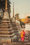 泰国修士在老古老塔前面走在Wat Pho寺庙在Bankgok,泰国 免版税库存图片