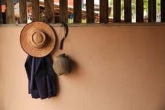 泰国农夫垂悬在墙壁上的制服 免版税库存照片